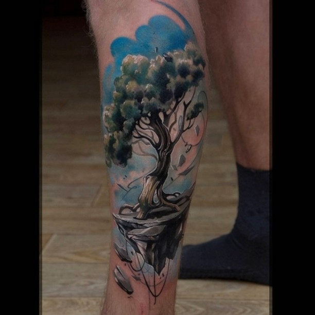 a beautiful tree on the clif on the blue sky background - tattoo on calf