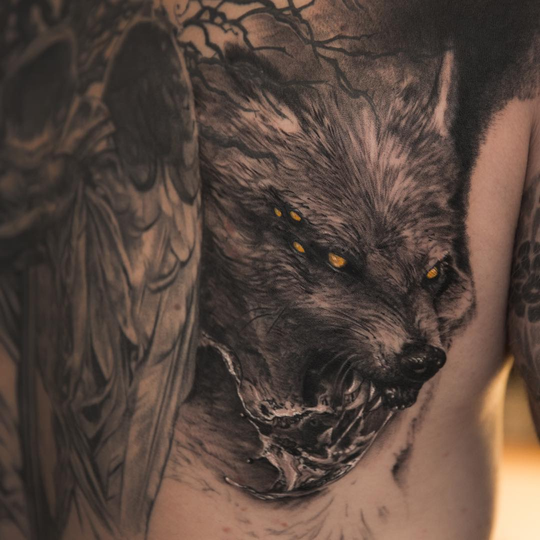 very angry looking Fenrir Tattoo inspired by Scandinavian Mythology. Realistic black and grey tattoo