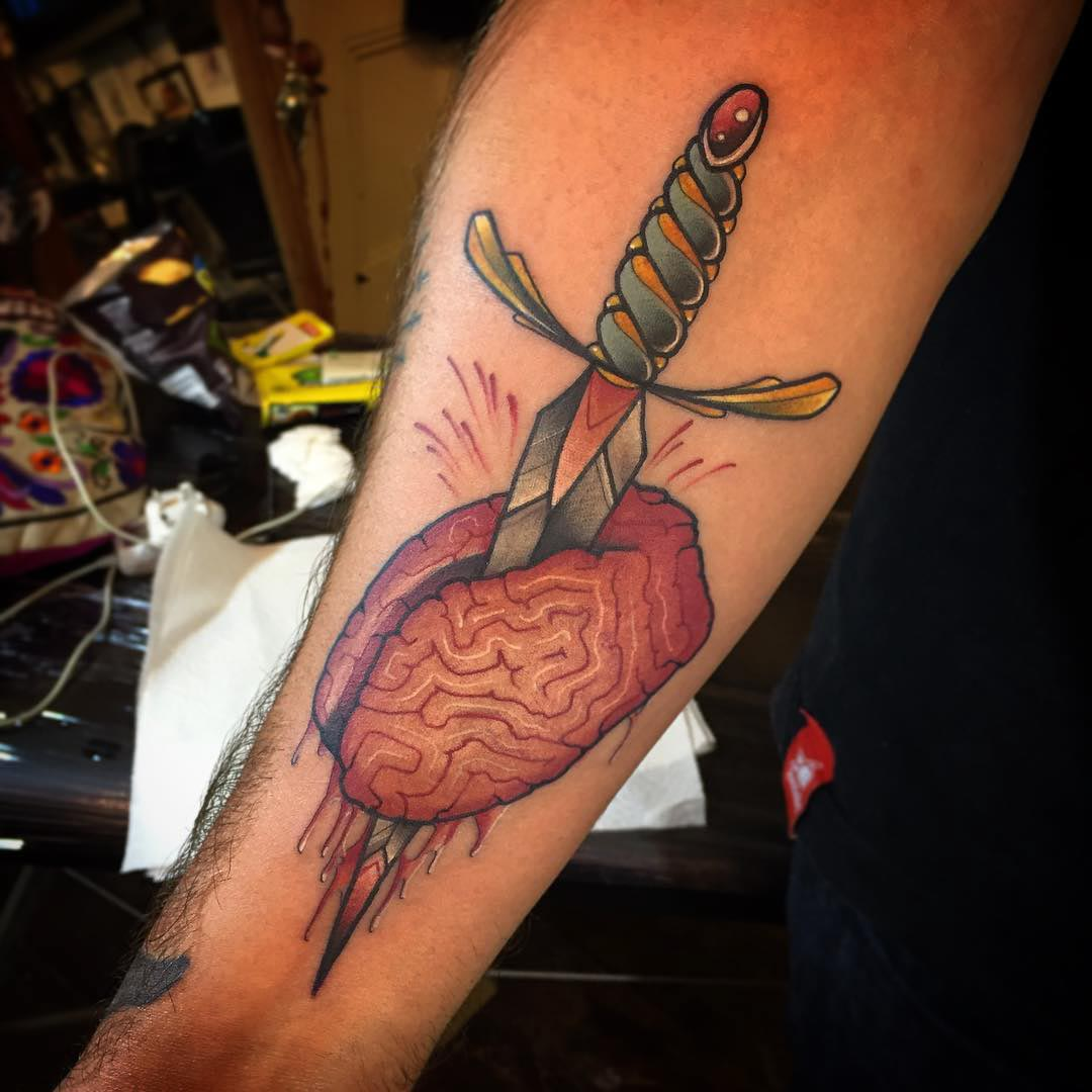neo-traditional tattoo on arm of dagger and brain
