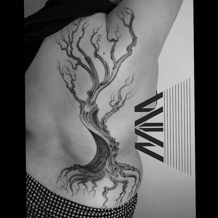 black and grey dead tree tattoo on the side of a body
