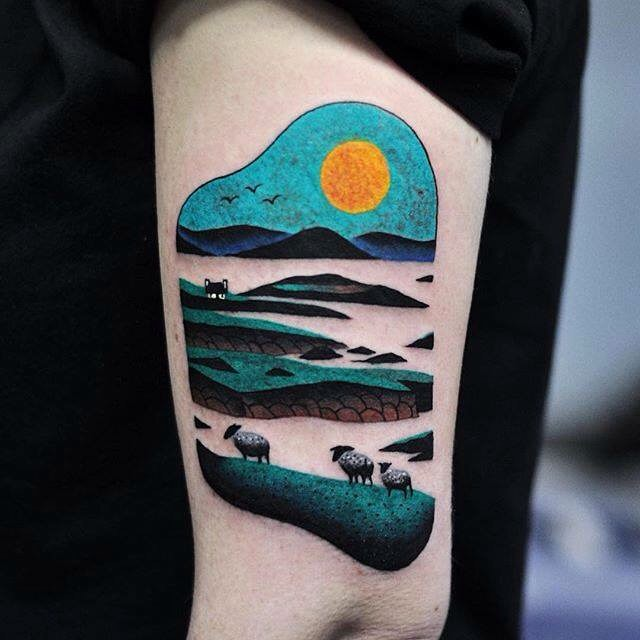 a tattoo on arm depicting sheeps in fields