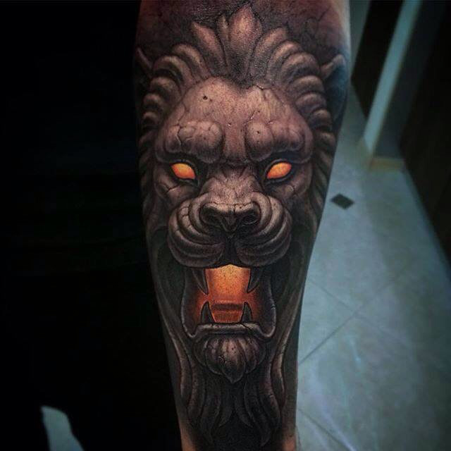 demonic stone lion tattoo on forearm