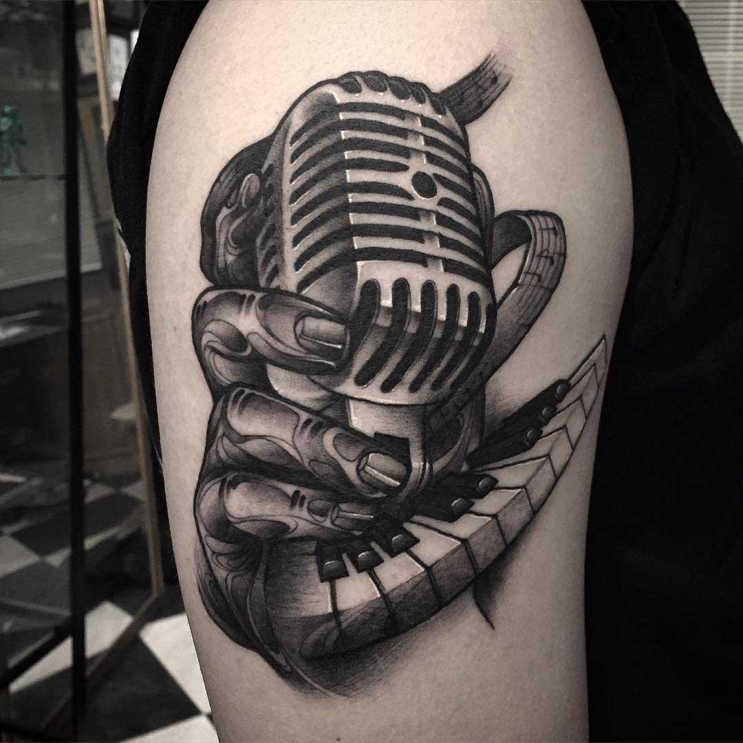 a vintage microphone tattoo on shoulder