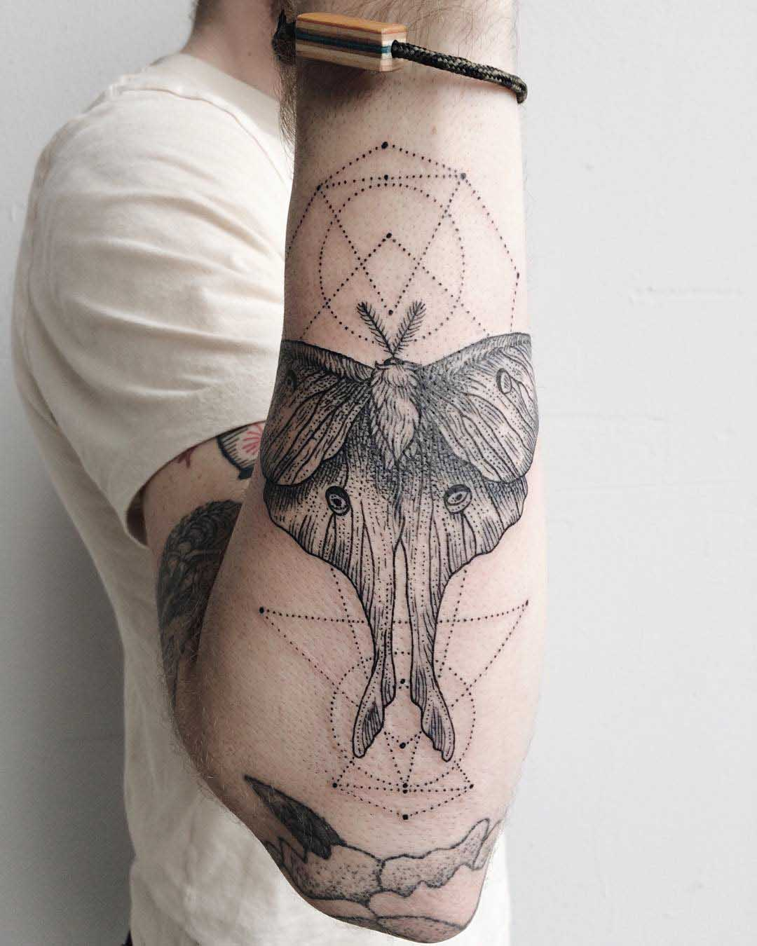 forearm tattoo of a moth and dots geometry