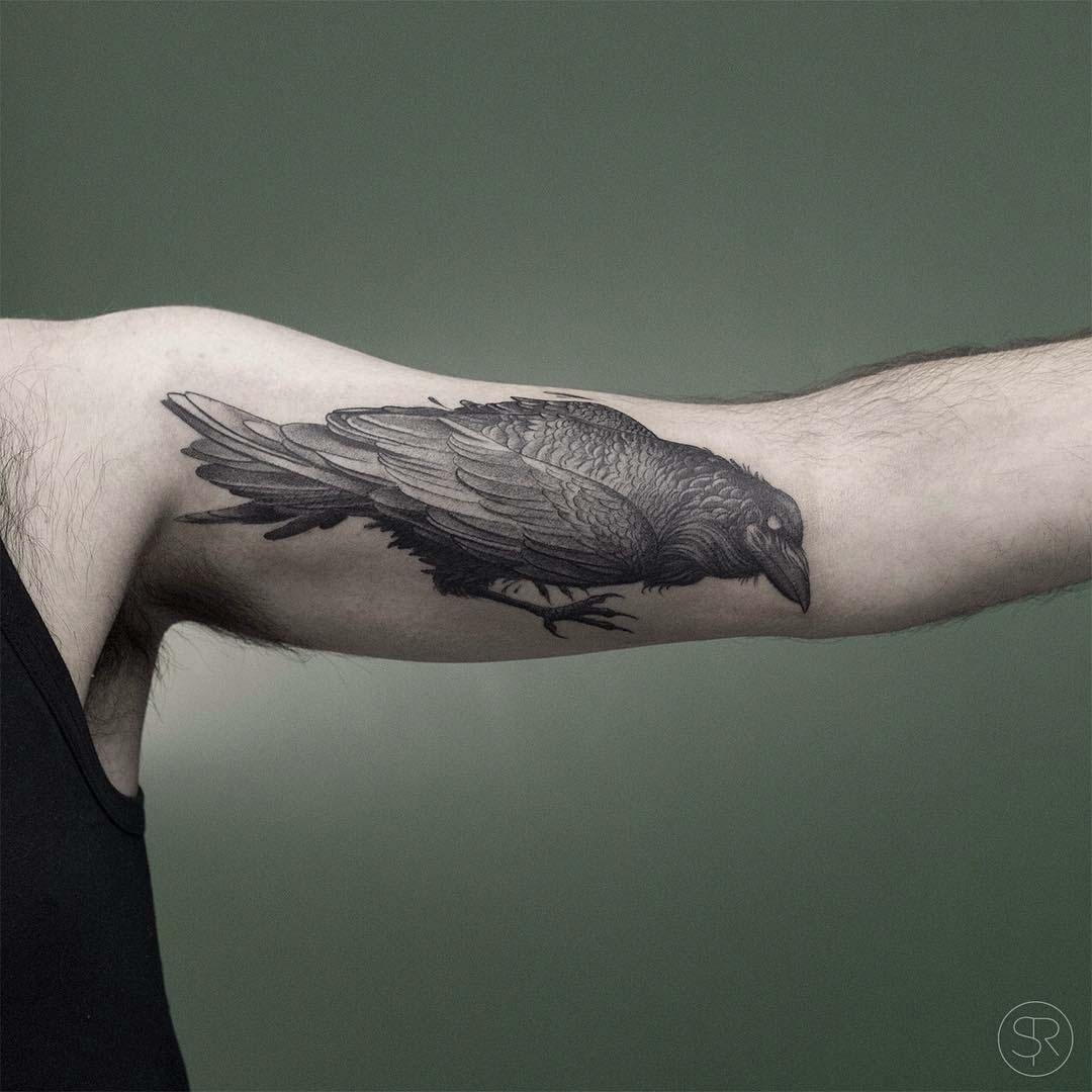 grey raven tattoo on bicep