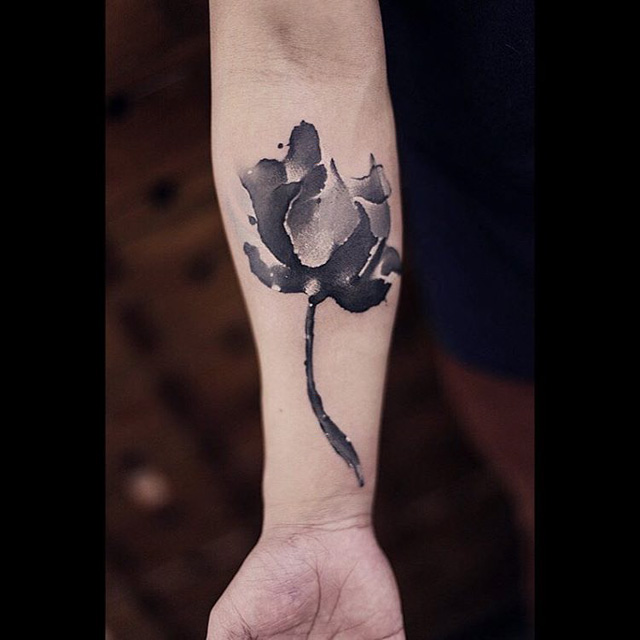 grey flower inner arm tattoo