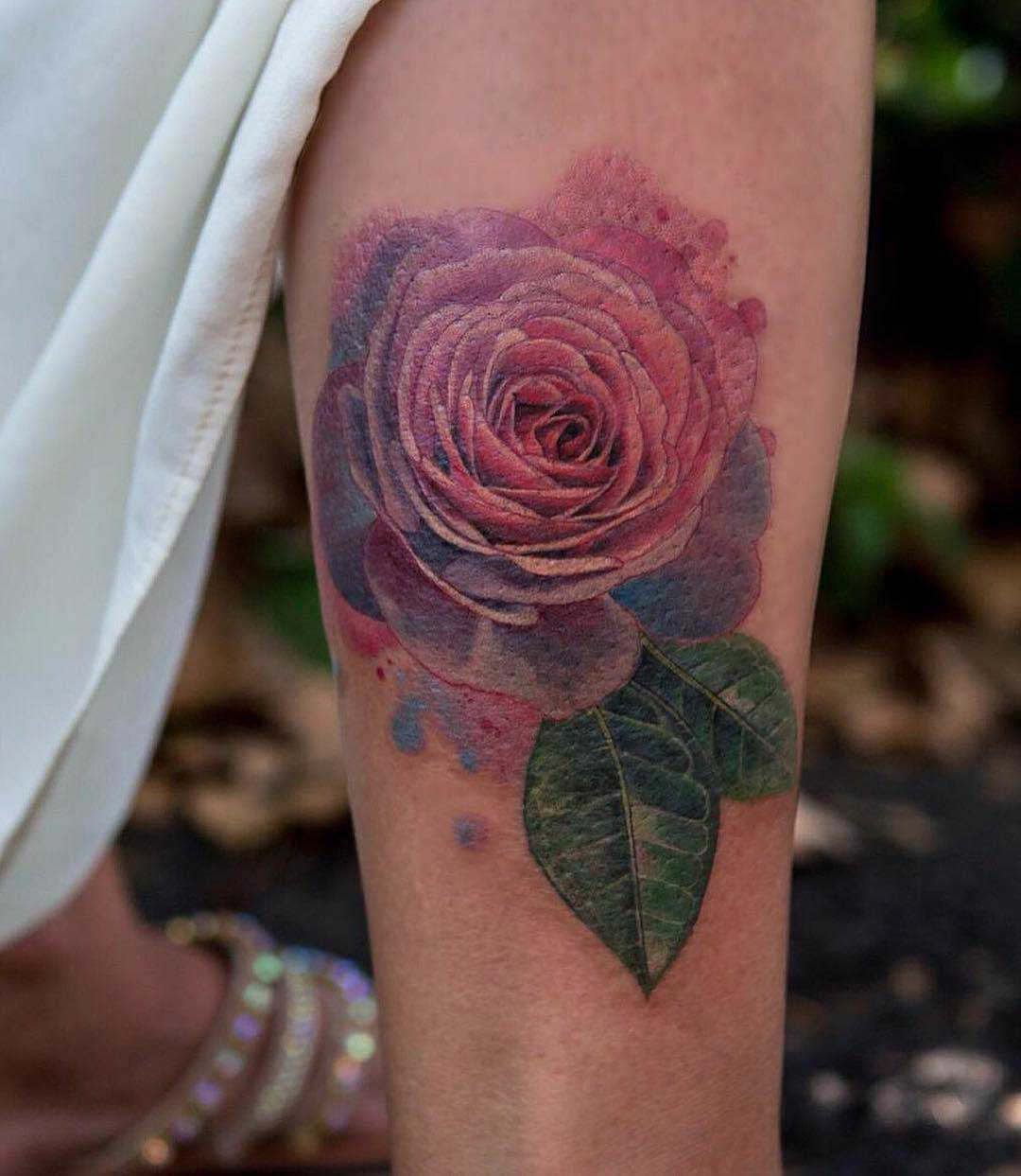 pink rose tattoo on forearm