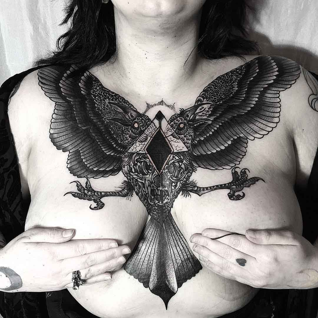 big crow tattoo on girl's chest