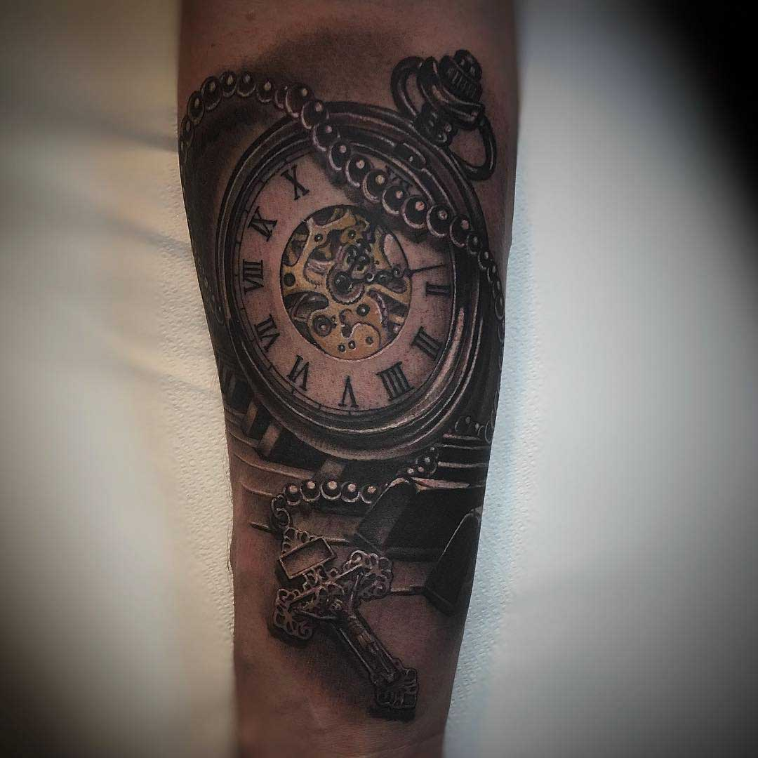 religious crux and pocket watch tattoo on arm