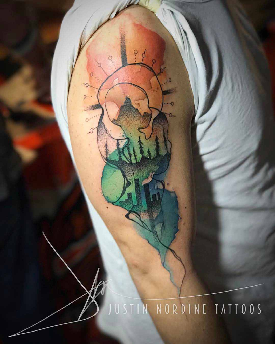 watercolor style nature and city tattoo on shoulder