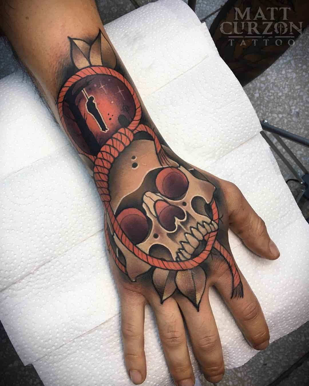 skull tattoo on hand with rope and hanged man
