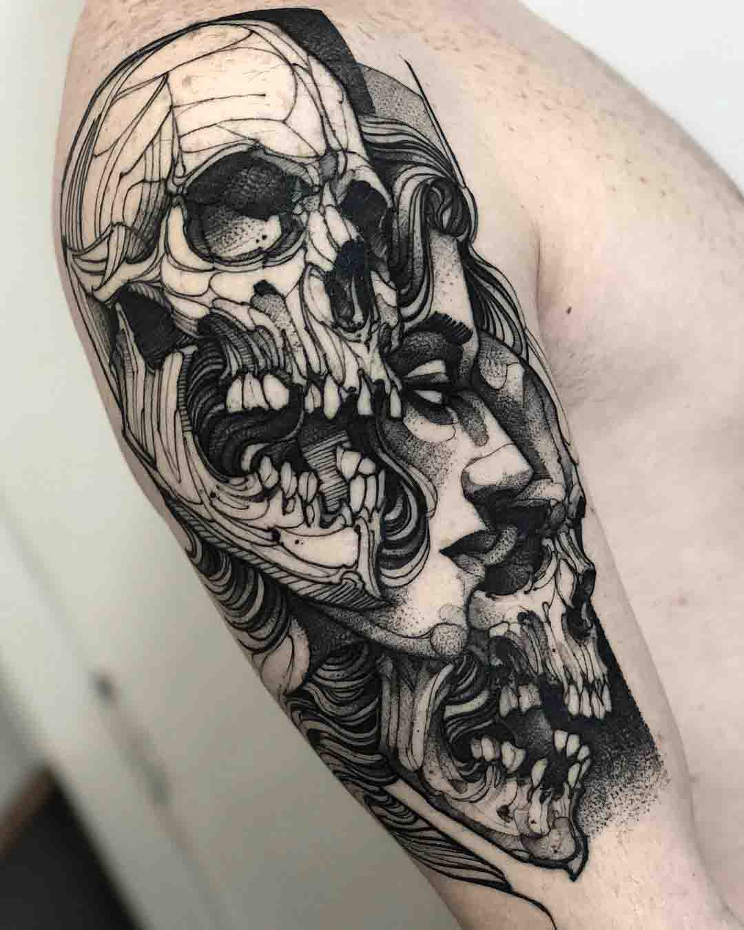Twos skulls and face tattoo on shoulder